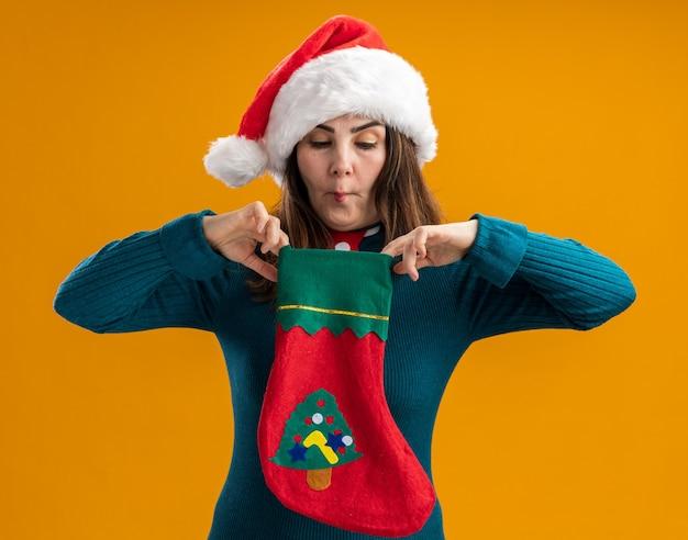 Впечатленная взрослая кавказская женщина в шляпе санта-клауса и галстуке санта-клауса держит и смотрит на рождественский чулок, делая рыбий рот изолированным на оранжевом фоне с копией пространства
