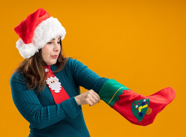 Впечатленная взрослая кавказская женщина в шляпе санта-клауса и санта-галстуке сует руку в рождественском чулке, изолированном на оранжевом фоне с копией пространства