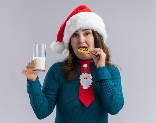Donna caucasica adulta impressionata con cappello da babbo natale e cravatta di babbo natale che tiene in mano un bicchiere di latte e mangia un biscotto isolato sul muro bianco con spazio per le copie