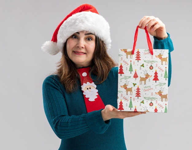 Impressed adult caucasian woman with santa hat and santa tie holding paper gift box isolated on white wall with copy space