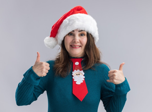 Impressed adult caucasian woman with santa hat and santa tie thumbs up isolated on white wall with copy space