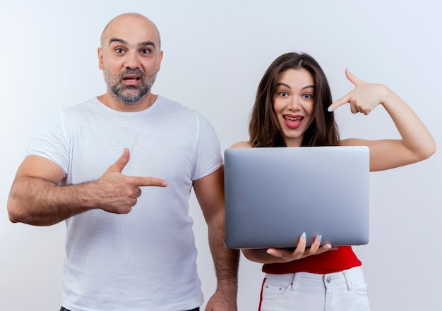 Impressed adult couple both looking woman holding laptop and both pointing at laptop