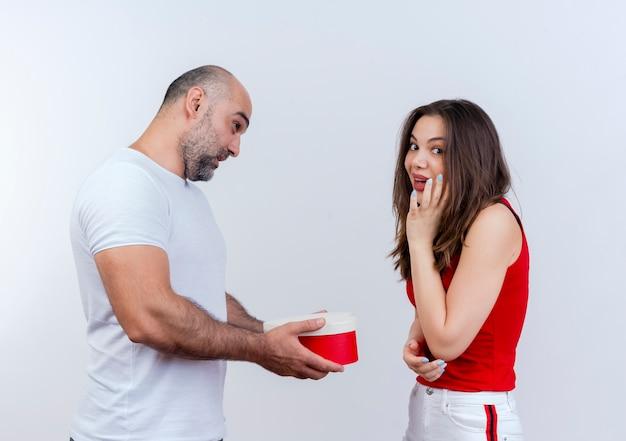 Impressionato coppia adulta uomo che tiene confezione regalo a forma di cuore guardando donna e donna che tocca il viso e guardando isolato