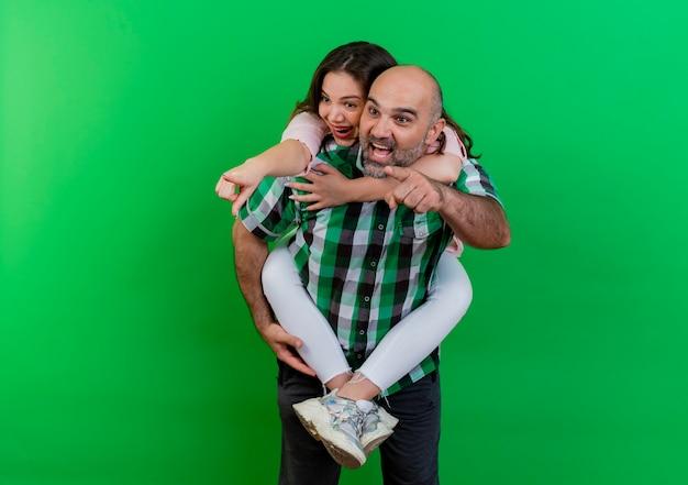 Impressionato coppia adulta uomo che tiene la donna sulla schiena sia guardando che indicando il lato isolato sulla parete verde con lo spazio della copia