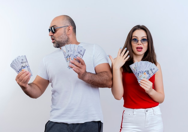 Impressed adult couple wearing sunglasses holding money man looking at side and woman keeping hand in air looking