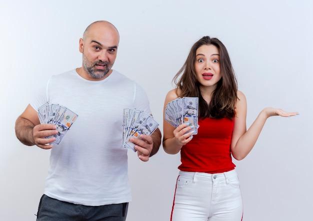 お金を持っていると見ている両方の空の手を示している感動した大人のカップルの女性
