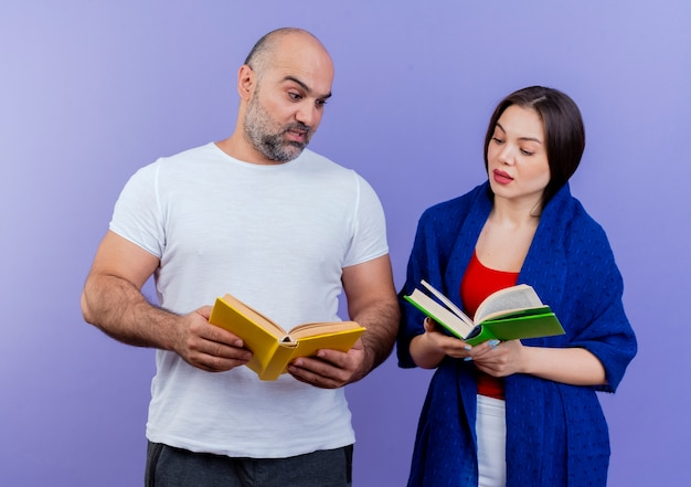 Impressionato coppia adulta donna avvolta in uno scialle tenendo il libro e guardando i libri a vicenda