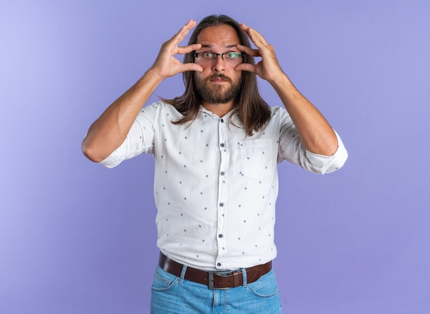 Impressed adult handsome man wearing glasses looking at camera making big eyes isolated on purple wall
