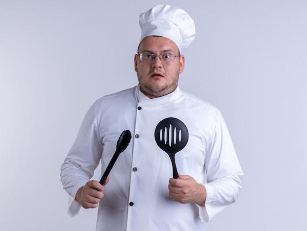白い壁に隔離された正面を見てトングとスロットスプーンを保持しているシェフの制服と眼鏡を身に着けている感動した大人の男性料理人