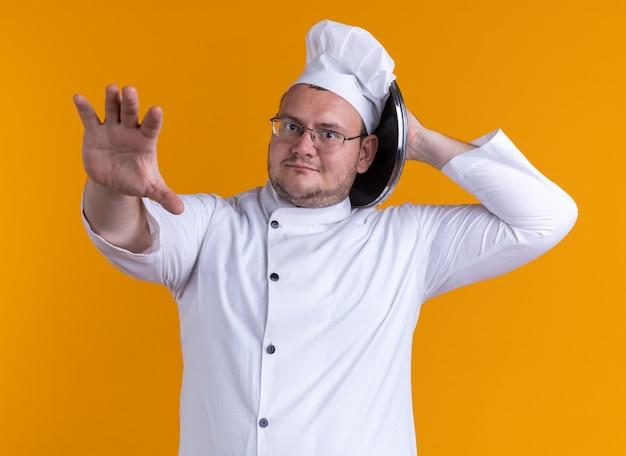 オレンジ色の背景に分離されたカメラに向かって手を伸ばして頭に触れて頭の後ろに鍋の蓋を保持しているカメラを見てシェフの制服とメガネを身に着けている印象的な大人の男性料理人