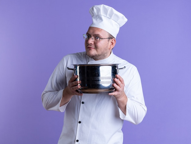 Impressed adult male cook wearing chef uniform and glasses holding pot looking at front isolated on purple wall