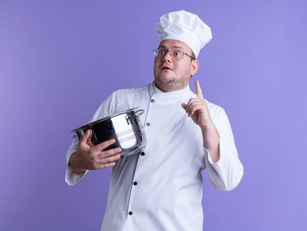 Impressed adult male cook wearing chef uniform and glasses holding pot looking at side pointing up isolated on purple wall