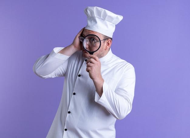 Cuoco maschio adulto impressionato che indossa l'uniforme dello chef e occhiali che toccano la testa guardando la telecamera attraverso lenti di ingrandimento isolate su sfondo viola con spazio di copia