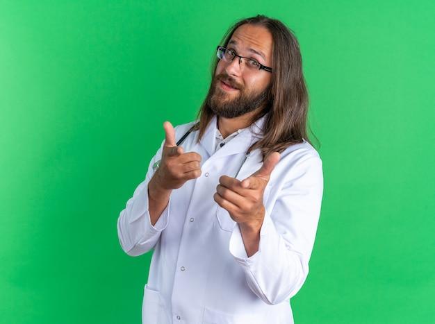 녹색 벽에 격리된 몸짓을 하는 카메라를 바라보는 안경을 쓰고 의료 가운과 청진기를 착용한 성인 남성 의사