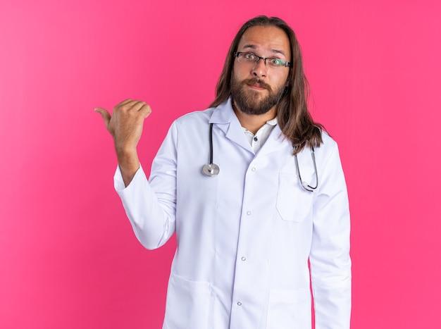 Medico maschio adulto impressionato che indossa accappatoio medico e stetoscopio con gli occhiali che guarda l'obbiettivo che punta al lato isolato sulla parete rosa