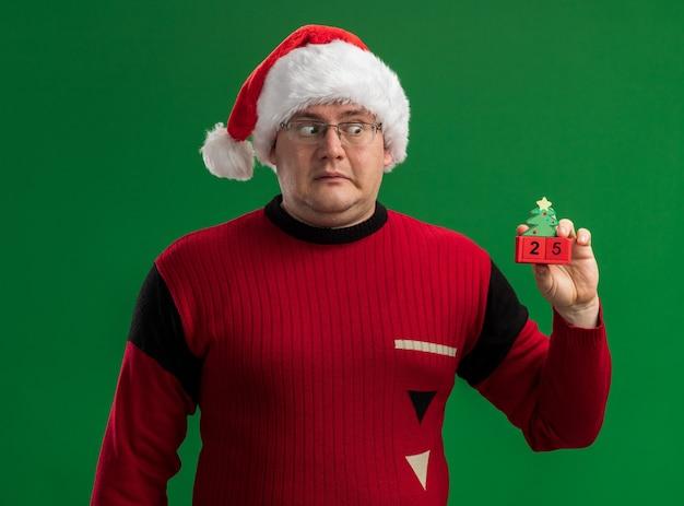 緑の背景で隔離の日付とクリスマスツリーのおもちゃを保持し、見て眼鏡とサンタ帽子を身に着けている印象的な大人の男 無料写真