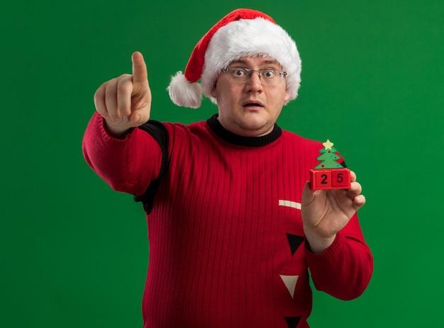 緑の背景に分離されたカメラを見て、日付を指しているクリスマスツリーのおもちゃを保持しているメガネとサンタ帽子を身に着けている印象的な大人の男