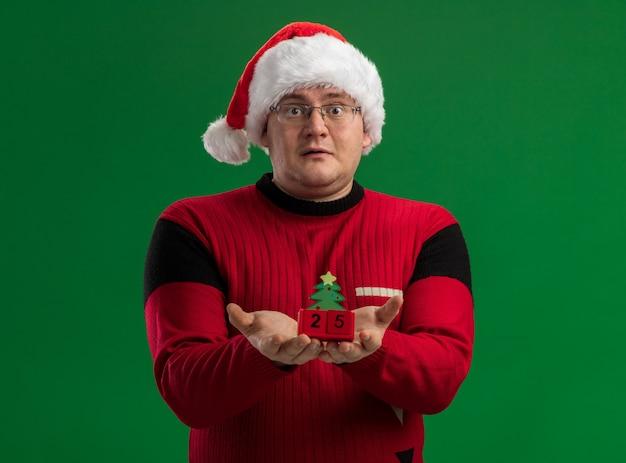 緑の背景に分離されたカメラを見て日付とクリスマスツリーのおもちゃを保持しているメガネとサンタ帽子を身に着けている印象的な大人の男