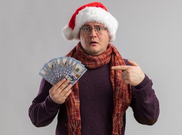 白い壁に隔離されたお金を保持し、指さし、首の周りにスカーフとメガネとサンタの帽子を身に着けている印象的な大人の男