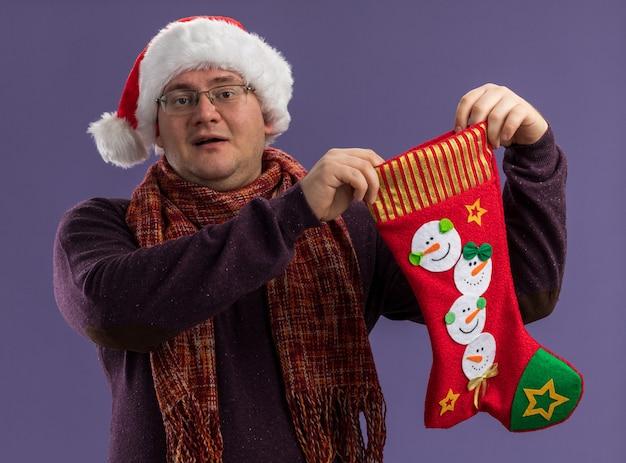 Впечатленный взрослый мужчина в очках и шляпе санта-клауса с шарфом на шее держит рождественский чулок, глядя в камеру, изолированную на фиолетовом фоне