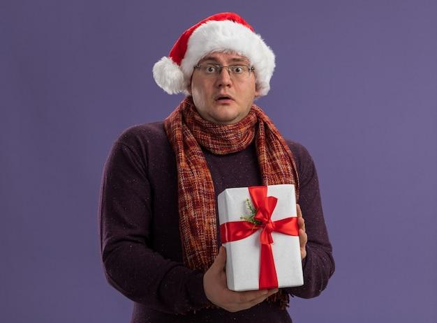보라색 배경에 고립 된 카메라를보고 선물 패키지를 들고 목에 스카프와 안경과 산타 모자를 쓰고 감동 성인 남자
