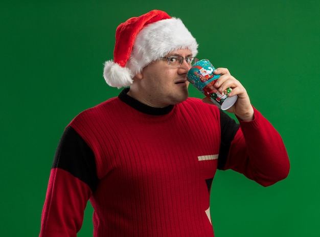 Impressed adult man wearing glasses and santa hat drinking coffee from christmas coffee cup looking at camera isolated on green background