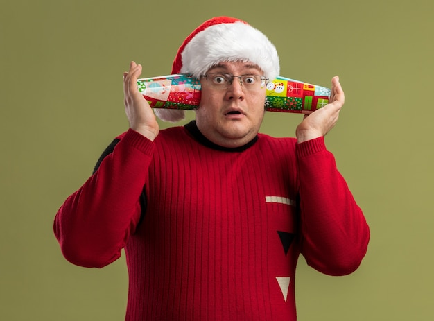 Impressed adult man wearing glasses and santa hat holding christmas coffee cups next to ears listening to secrets looking at camera isolated on olive green background