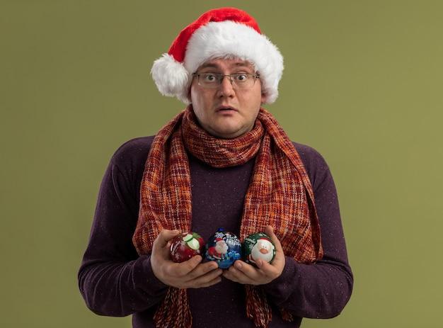 Uomo adulto impressionato con gli occhiali e cappello da babbo natale con sciarpa intorno al collo tenendo palline di natale guardando la fotocamera isolata su sfondo verde oliva