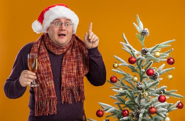 Impressionato uomo adulto con gli occhiali e cappello da babbo natale con sciarpa intorno al collo in piedi vicino all'albero di natale decorato con in mano un bicchiere di champagne guardando il lato rivolto verso l'alto isolato sul muro arancione
