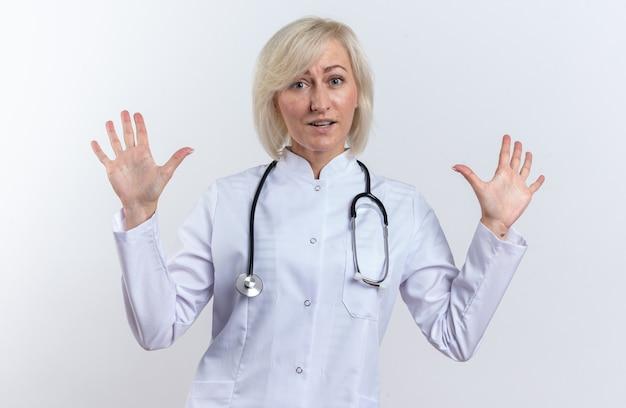 コピースペースのある白い壁に隔離された上げられた手で聴診器が立っている医療ローブの印象的な大人のスラブ女性医師