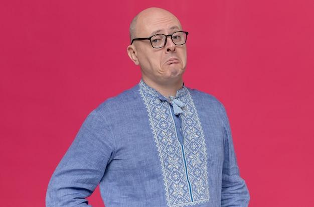 Impressed adult slavic man in blue shirt wearing glasses