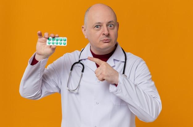 Uomo slavo adulto impressionato in uniforme da medico con stetoscopio che tiene e punta al blister della medicina