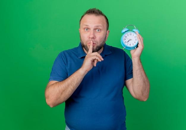 Впечатленный взрослый славянский мужчина держит будильник, делая жест тишины, изолированный на зеленой стене с копией пространства