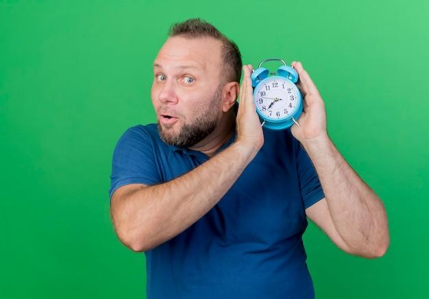 Впечатленный взрослый славянский мужчина держит будильник, глядя изолированным на зеленой стене с копией пространства