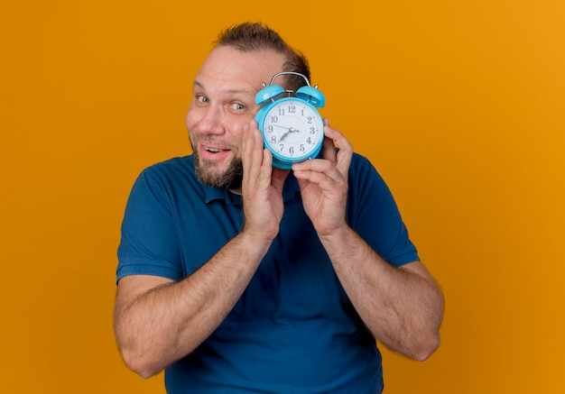 Impressed adult slavic man holding alarm clock near head and looking from behind it