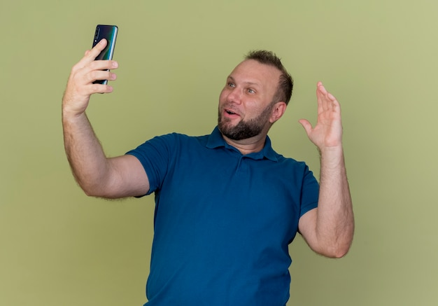 Впечатленный взрослый славянский мужчина держит и смотрит на мобильный телефон, держа руку в воздухе
