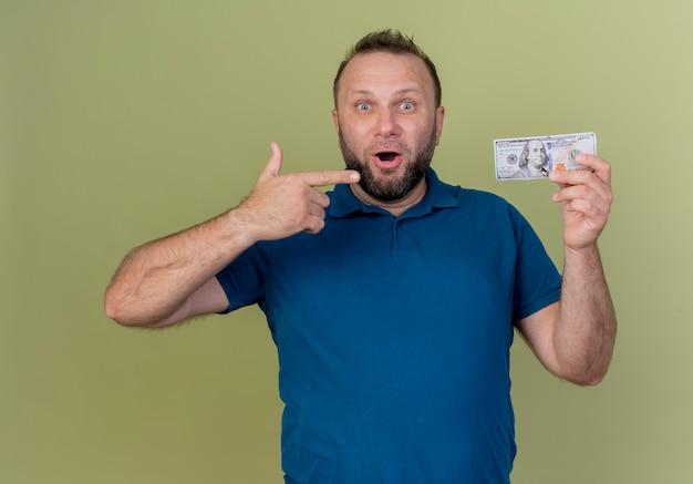 Впечатлен взрослый славянский мужчина, держащий и указывая на деньги