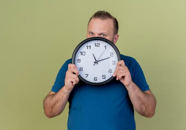 Впечатленный взрослый славянский мужчина держит часы и смотрит из-за них