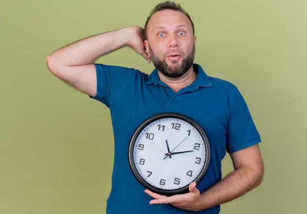 Orologio della holding dell'uomo slavo adulto impressionato che mette la mano dietro la testa
