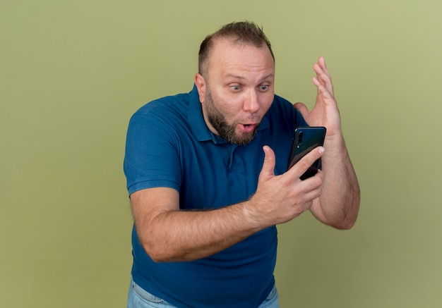Impressed adult slavic man holding and looking at mobile phone keeping hand in air