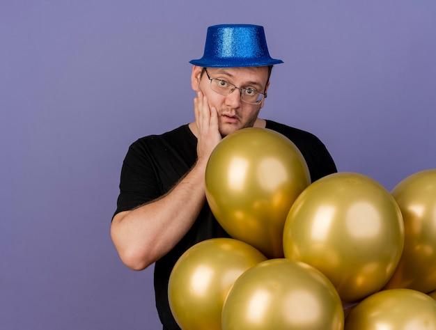 파란색 파티 모자를 쓰고 광학 안경을 쓴 성인 슬라브 남자가 얼굴에 손을 대고 헬륨 풍선으로 서 있습니다.