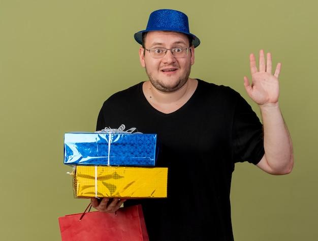 파란색 파티 모자를 쓰고 광학 안경에 인상적인 성인 슬라브 남자가 제기 손으로 선물 상자와 종이 쇼핑백을 보유하고 있습니다.