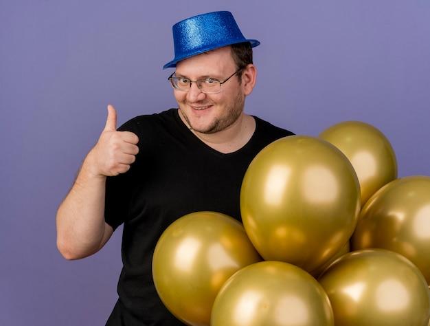 파란색 파티 모자를 쓰고 광학 안경을 쓴 성인 슬라브 남자가 헬륨 풍선으로 서 엄지 손가락
