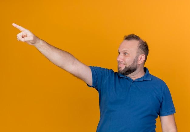 Uomo slavo adulto colpito che osserva e che indica al lato isolato