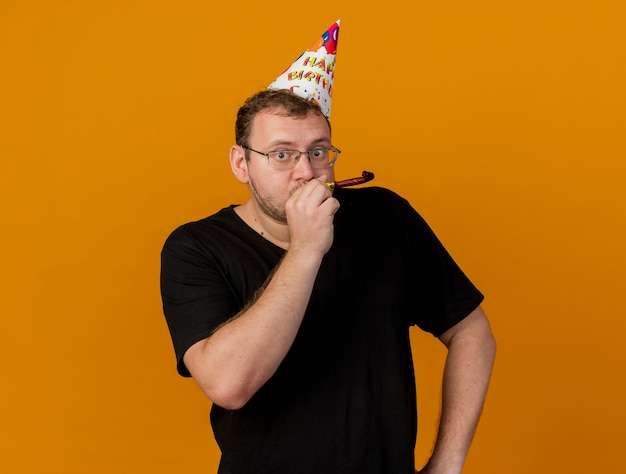 Impressed adult slavic man in optical glasses wearing birthday cap blowing whistle