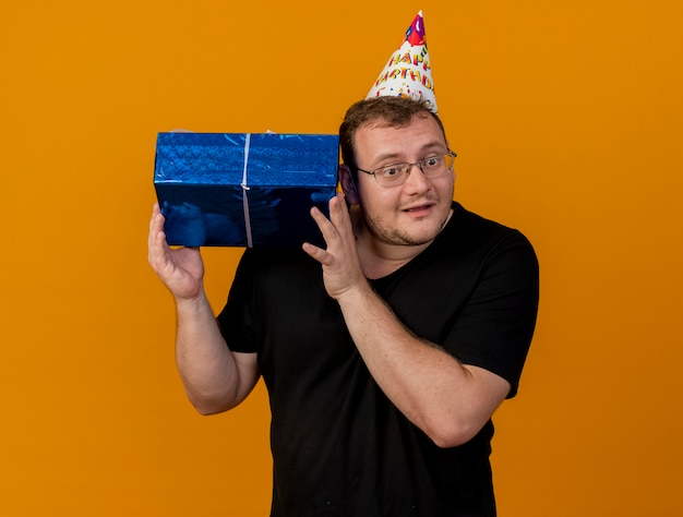 Impressed adult slavic man in optical glasses wearing birthday cap holds gift box close to ear trying to hear
