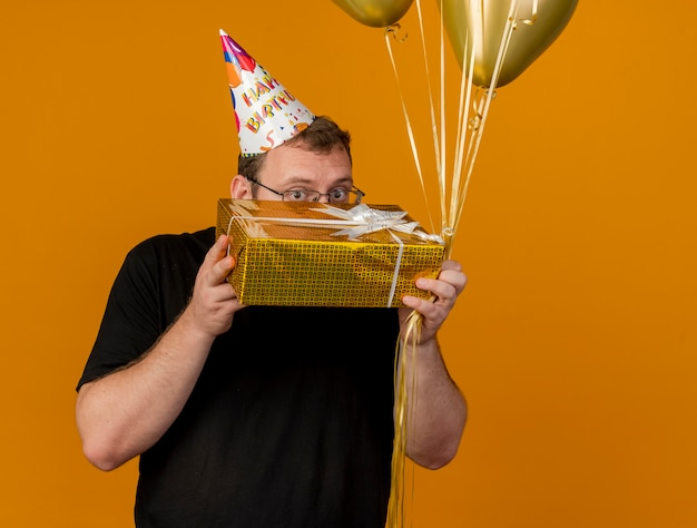 Impressed adult slavic man in optical glasses wearing birthday cap holds helium balloons and gift box