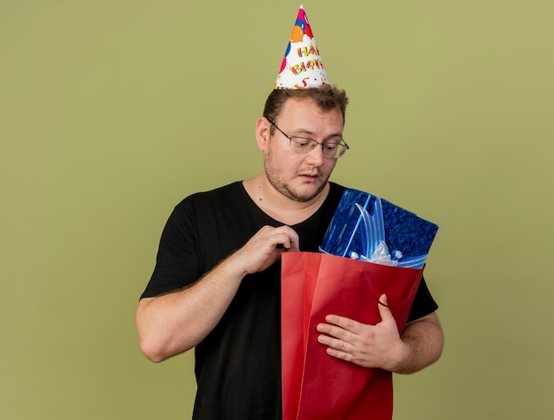 Impressed adult slavic man in optical glasses wearing birthday cap holds and looks at gift box in paper shopping bag