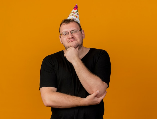 Impressionato uomo slavo adulto in occhiali ottici che indossa un cappello di compleanno mette la mano sul mento guardando la telecamera