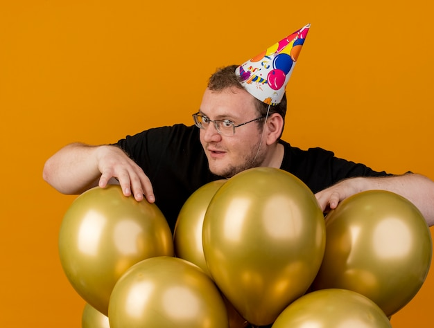 Impressed adult slavic man in optical glasses wearing birthday cap stands with helium balloons